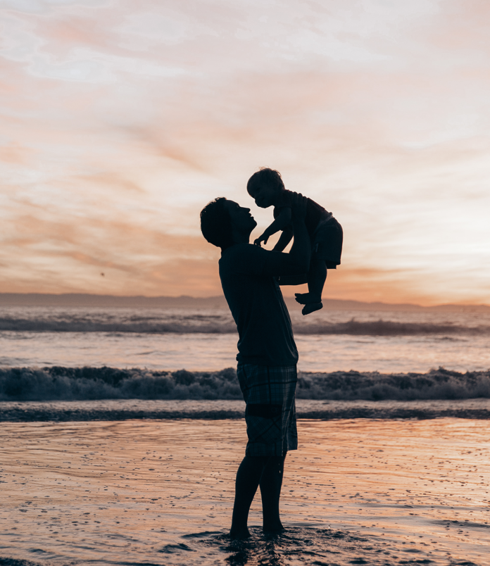 Father supporting Child over head at beach